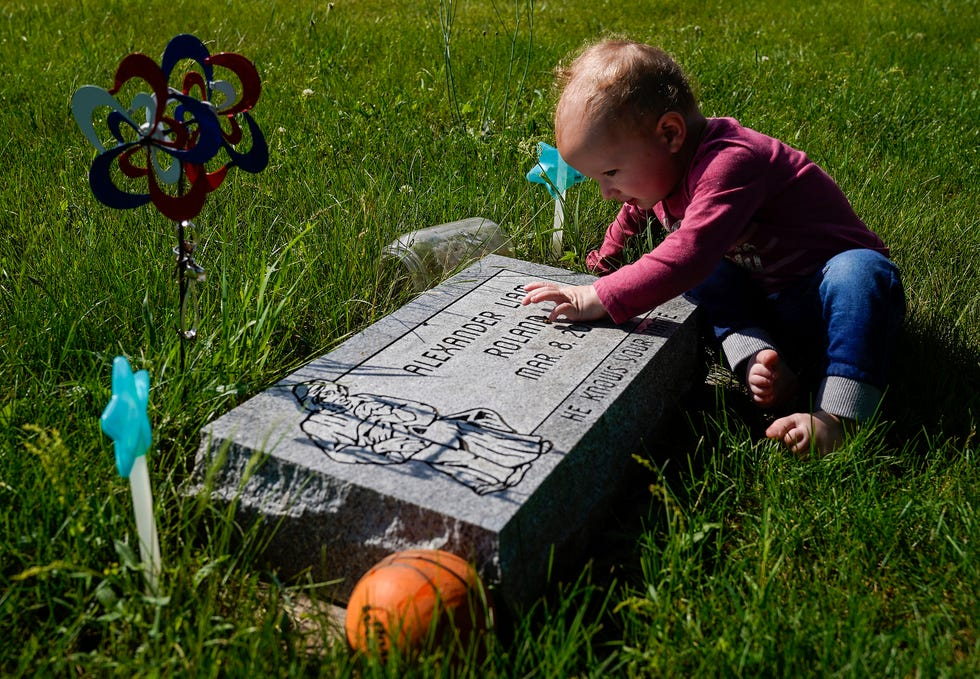 Desmond Roland's daughter, Ellamae, touches the grave of Alexander Liam Roland on June 9 at the Prairie Street Cemetery in Elkhart.