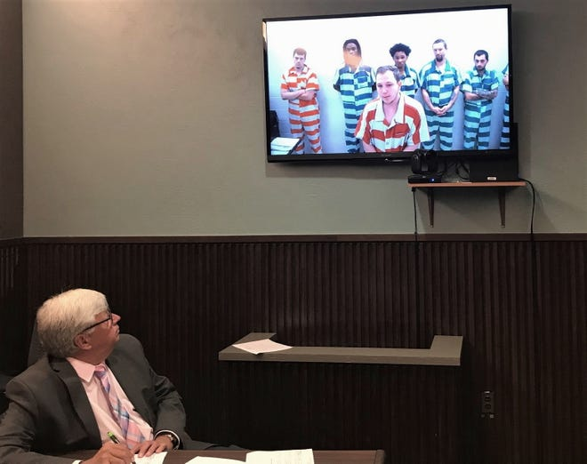 Chief Deputy Doug Laser, left, listens as a $1 million cash and personal recognizance bond is ordered for Izzac Lawhorn, in foreground of video, in Mansfield Municipal Court on Monday. Lawhorn, 19, of Bellville, is charged with felonious assault, a first-degree felony,  in the stabbing of a 74-year-old woman on June 3 on Brookfield Drive.