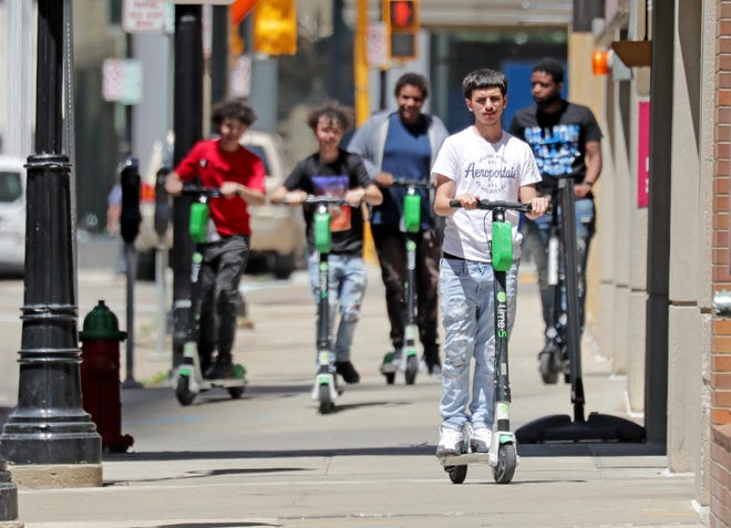 A group of people ride electric scooters on the sidewalk along North Water Street near East Wisconsin Avenue in Milwaukee on Monday, June 14.