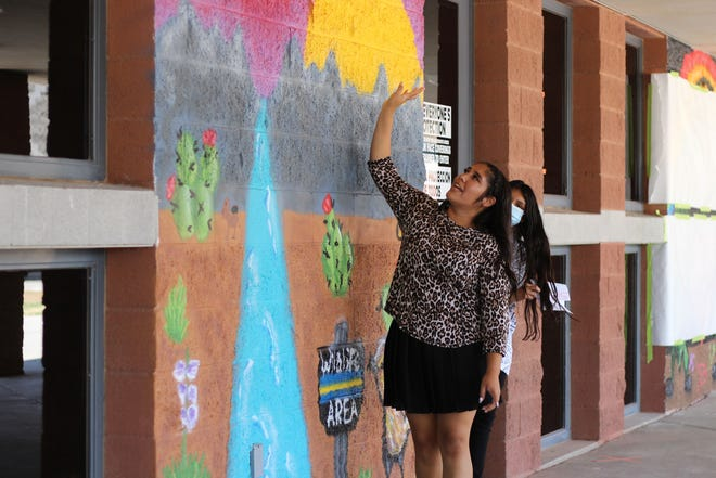 """Tahlor Triolo explains her work on the mural """"Preserve Wildlife"""" at an unveiling at Organ Mountain High School on Monday, June 14, 2021. During extended learning time, OMHS partnered with Cruces Creatives, a local group that provides supplies and space for creativity through art, to teach students about the history of spray painting."""