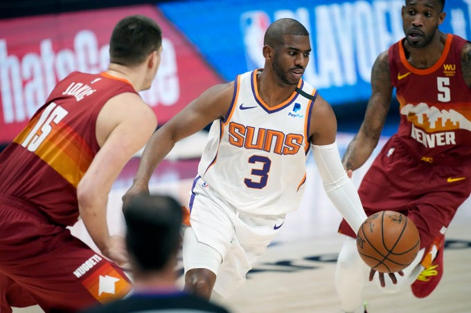 Phoenix Suns guard Chris Paul, center, drives to the rim between Denver Nuggets center Nikola Jokic, left, and forward Will Barton in the first half of Game 4 of an NBA second-round playoff series Sunday, June 13, 2021, in Denver. (AP Photo/David Zalubowski).