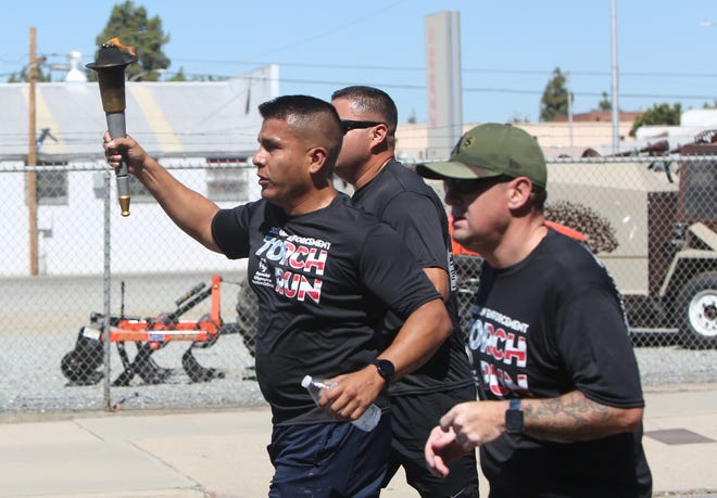 Tulare Police Detective Art Cabello carries the 'Flame of Hope' Special Olympics' torch alongside two officers, two other officers followed (not pictured), on a two-mile run through downtown Tulare on June 14, 2021. Nine Tulare County law enforcement agencies participated in the event, a first for the county.