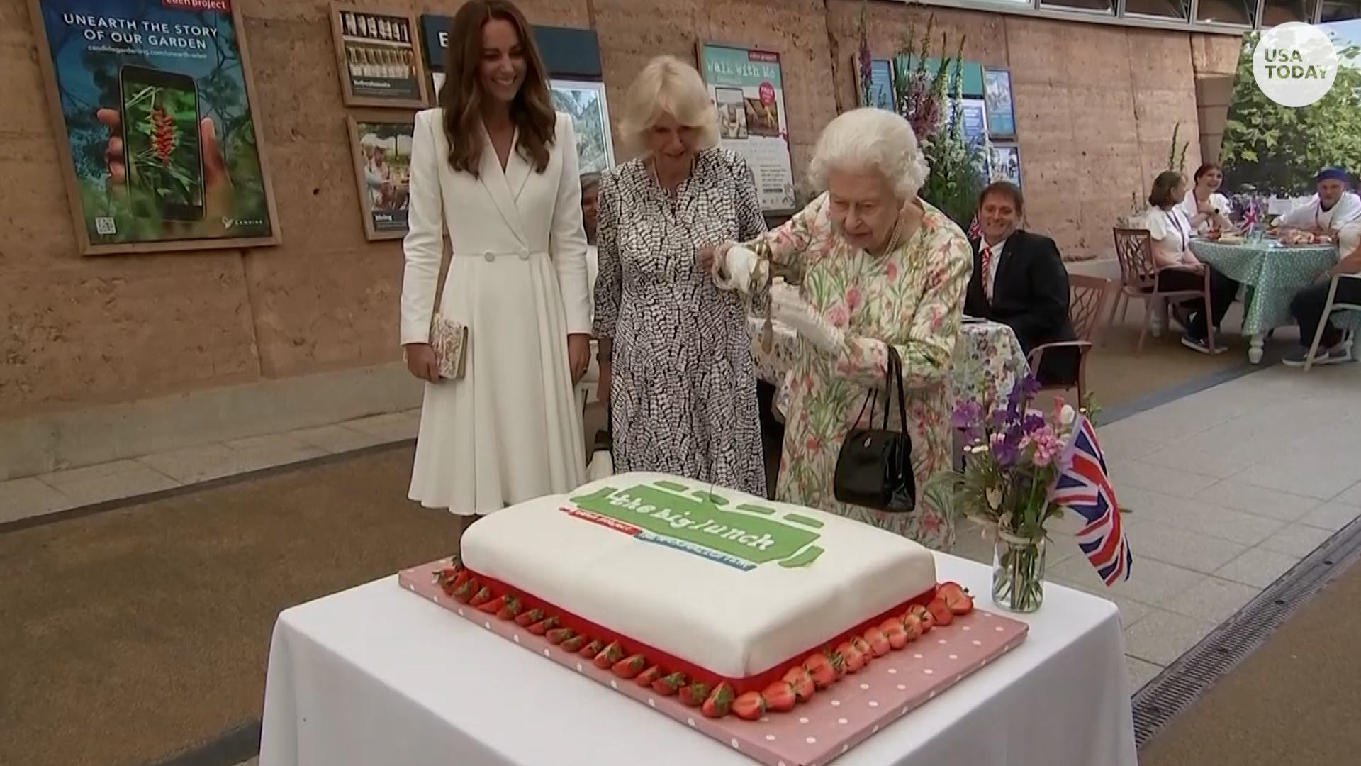 Queen Elizabeth II cuts a cake with a massive ceremonial sword