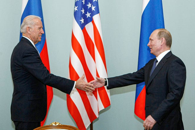 Then-Vice President Joe Biden, left, shakes hands with then-Russian Prime Minister Vladimir Putin in Moscow, Russia, on March 10, 2011.