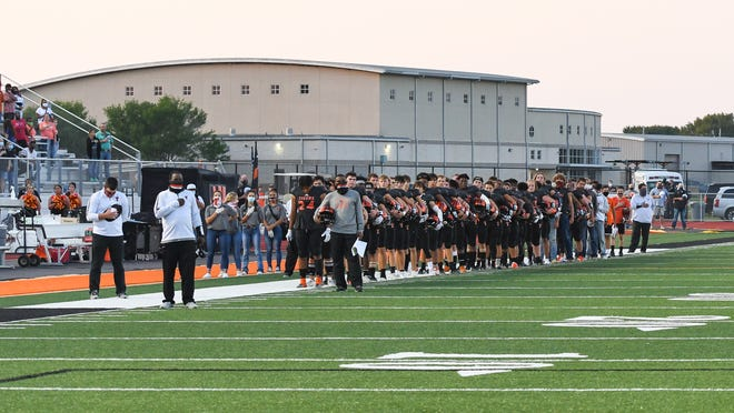 Smithville players line the sideline during the playing of the National Anthem before a game last season.