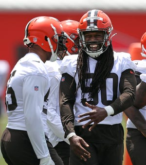 Cleveland defensive end Jadeveon Clowney, right, shares a laugh with new teammate Myles Garrett. If Browns fans don't have to pretend Clowney is healthy, he should help the defense take a jump.