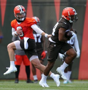 Cleveland Browns quarterback Baker Mayfield (6) hands the ball off to Cleveland Browns running back Nick Chubb (24) during an NFL football practice at the team's training facility, Tuesday, June 15, 2021, in Berea, Ohio. [Jeff Lange / Akron Beacon Journal]