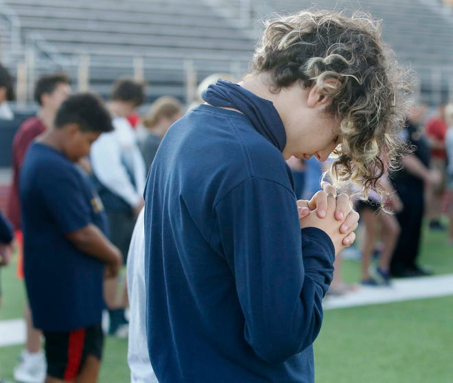 Atticus Clum, 13, joins other in prayer during a prayer vigil for Shondray Fisher, 12, and his family at the Tallmadge High School football stadium Monday, June 14, 2021 in Tallmadge, Ohio. Shondray suffered serious injuries when he was struck by a car while riding his bicycle last week.