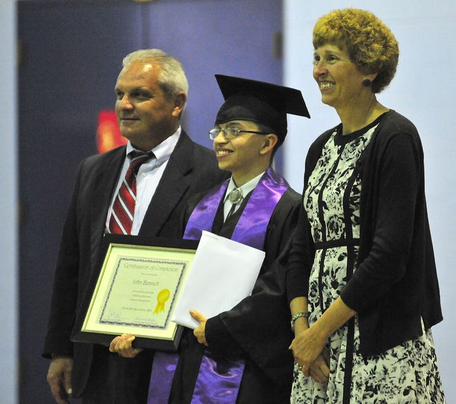 Dale-Roy School's John Bennett smiles between Dave Ashley, superintendent of Ashland County Board of Developmental Disabilities, and Dr. Tammy Stevens, director of student services for Ashland City Schools, on Tuesday, June 8 at Dale-Roy. Bennett and Fayth Windsor, both from Ashland City Schools, graduated from Dale-Roy School last week.