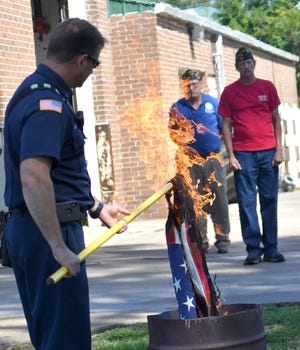 Sylvania Firefighter Charlie Milton holds a retired burning American flag Monday morning during the VFW and DAR Flag Day ceremony behind the city fire department.