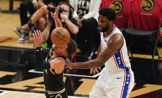 Philadelphia 76ers center Joel Embiid (21) fouls Atlanta Hawks guard Trae Young (11) during the first half of Game 4 of a second-round NBA basketball playoff serieson Monday, June 14, 2021, in Atlanta. (AP Photo/Brynn Anderson)