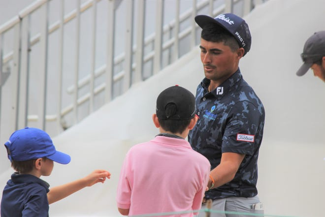 Kathryn McCartha's grandsons, Lucas and Jacob, receive a golf ball from local golfer Bryson Nimmer following his third round at the Palmetto Championship at Congaree.