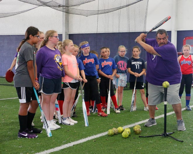 Early High School softball coach Alfonso Chavez gives hitting instructions at the one-day softball camp Tuesday morning in the high school's Big Room. The camp was for incoming third-through-ninth-graders. Chavez told the girls they would be learning what high school softball players are taught.
