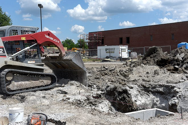 Construction workers dump gravel around a storm sewer box in the parking lot of Rock Bridge Elementary School on Friday.