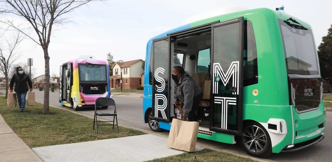 Sherri Rowell, left, and Donna Brittman organize food bags for Linden residents. A self-driving shuttle delivers food from the St. Stephen's Community Center to the Rosewind Community Center, about a mile away.