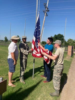 Robert Jones, Muhammad Tieco, Glenwood Gerow, and Kagan Kingsbury lower a flag during Flag Day in Dodge City on Monday.