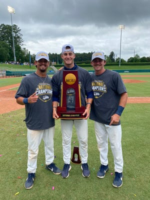Wingate's Brody McCullough holds the NCAA Division II national championship trophy. Flanking him are teammates Carson Simpson (left) and Jed Bryant. [Contributed photo]