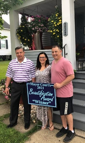 """Ellwood City Mayor Anthony Court (left) recently presented his first """"Mayor Court's 2021 Beautification Award"""" to Emrica Shaffer (center) and Michael Frisk at 232 Hazel Ave. in the borough. There are five more winners to be presented with this award from Mayor Court, with nominations to be sent to either his office or the Ellwood City Police Department."""