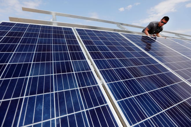 In this file photo Nick Green, with Mohrfeld Electric of Fort Madison, works on installing solar panels, at the Southeastern Community College's Keokuk campus. The city of Burlington is looking into installing solar panels on city buildings.