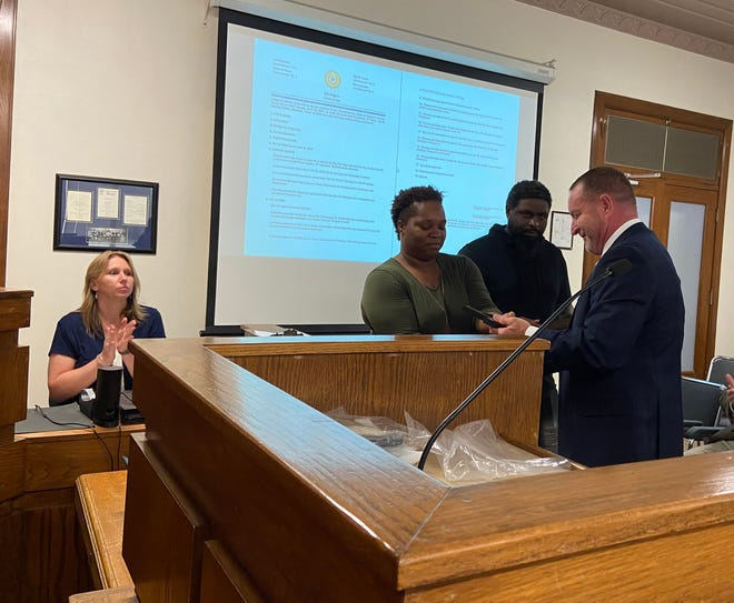 Grayson County District Attorney Brett Smith presents the courage award to Brandon and Crystal Powell Tuesday.
