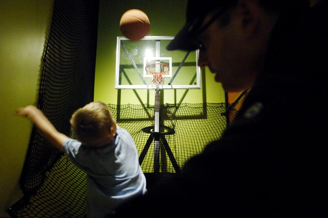 In this 2013 file photo, Ben Geers, 6, of Peoria throws basketballs at an oscillating hoop with his father, Christopher, at the IHSA Peak Performance exhibition at the Peoria Riverfront Museum.
