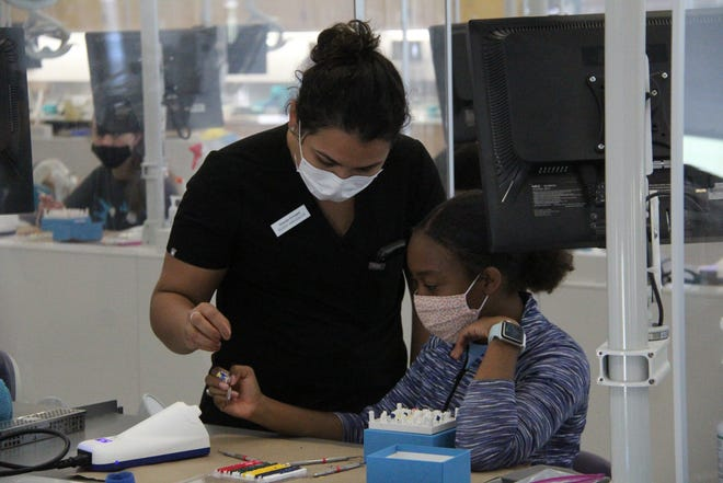 ATSU student ambassador Yessenia Enriquez works with a student on a wax tooth molding exercise as part of the Summer Healthcare Program offered at ATSU and Truman.