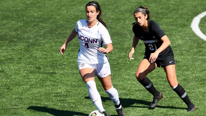 UConn freshman and Marlborough resident Lucy Cappadona dribbles the ball past Providence College forward Kyla Gallagher on March 21.