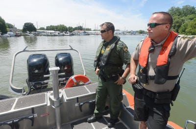 Brian Budd from the U.S. Border Patrol (left) and Deputy Brian Francisco from the Monroe County Sheriff's Office's marine division leave Bolles Harbor in a boat to patrol waters of Lake Erie in July, 2016.