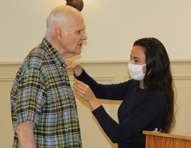 Catherine Spare places the Paul Harris Fellow Award pin on her father during a June 3 ceremony at the M.M. Ewing Continuing Care Center.