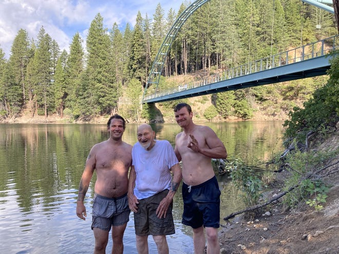 Don Berry, center, celebrated his upcoming 90th birthday with a celebratory jump. He's flanked by two younger men who aided him as he paddled to Lake Siskiyou's shore.