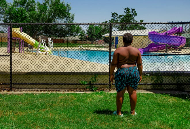 Decati Crandell, 10, stares at the water after walking to Oklahoma City's Northeast Community Center Pool on Tuesday to swim, only to find out the pool was closed due to a lifeguard shortage.