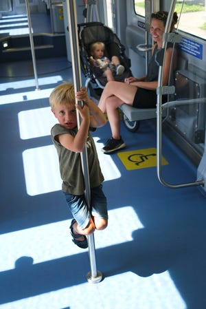 Mallory Carter, sits with her son Miles, in stroller, and watches her other son, James, hang on a pole in an Oklahoma City Streetcar on June 14.
