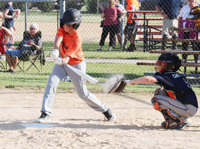 DeWald Construction batter Ben Melchers hits the ball after connecting with Pontiac Police Association catcher Drew Christensen's glove during Monday's Little League game at the Rec-Plex. Melchers was awarded first base for catcher's interference that also forced in a run in DeWald's 6-5 come-from-behind win.