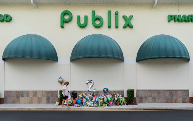A woman left a teddy bear at a memorial in front of a Publix Super Market in Royal Palm Beach, Florida on June 13, 2021. Timothy Wall shot and killed a 69-year-old grandmother and her toddler grandson inside the store before killing himself on Thursday.