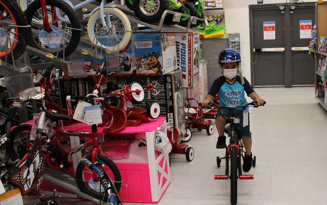 Lakemont Elementary second-grader Juan Diego Robles rides a bike at the Petersburg Walmart on June 10 to see if it is a good fit.