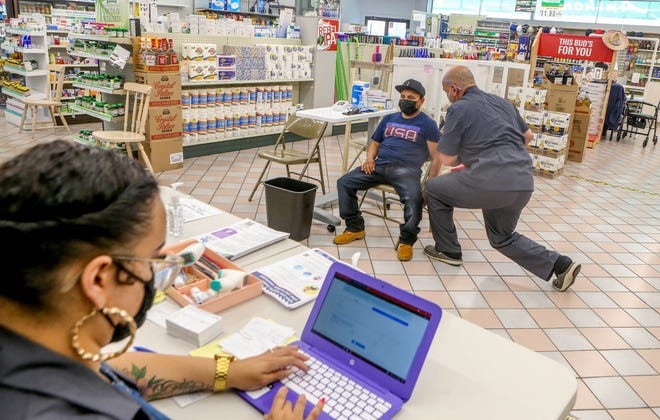 At Anthony's Pharmacy in Providence on Tuesday, pharmacist Peter Solomon gives Manuel Saquic his vaccine injection while Rosa Montes prints out his card.