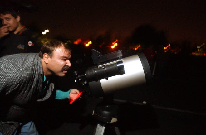 Doug Christensen lines up his telescope to look at a total lunar eclipse on Oct. 26, 2004, in the Shima 2 parking lot at San Joaquin Delta College in Stockton.