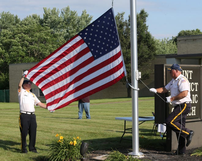 Richard Biedenbach, left, and John Hornbrook, of American Legion Post 44, raise the Stars and Stripes during a Flag Day ceremony at St. Mary & St. Benedict Church in Canton on Monday.