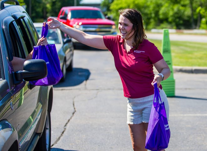 Jessica Springer with Spectrum Health helps distribute bags of fruit and vegetables Tuesday, June 15, 2021 at the Niles-Buchanan YMCA.