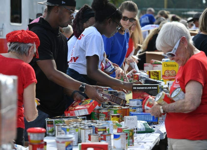 Volunteers help sort donated food for the Mayors' Feed the Hungry Program in November 2019. Donations will be collected on June 19 at Nathan Benderson Park.