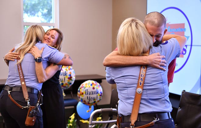 Car crash victim Matt Reich, right, hugs Manatee County EMS charge paramedic Karleigh Alday, while Matt's sister, Allison Kallevig, hugs paramedic Lydia Wilkinson, Tuesday during a reunion the Matt requested.  Alday and Wilkinson were the paramedics who responded to the 911 call when Matt was struck by a car when riding his bicycle. He credits them with saving his life and wanted to publicly thank them.