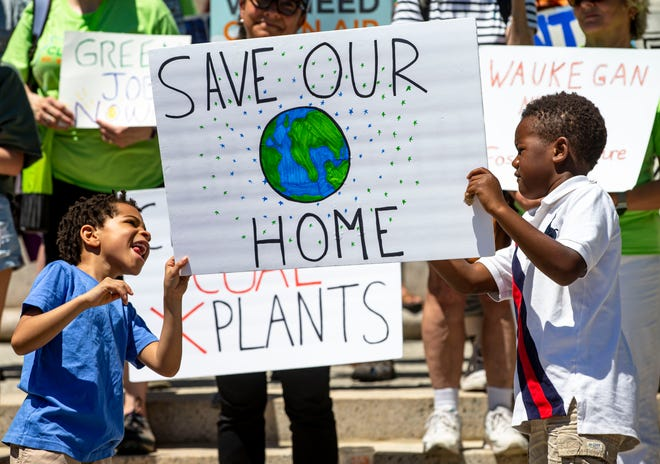 """Kaiden Trotter, 6, left, and Tise Ogunrinde, 7, join together to hold up a sign for the """"Rally for a Fossil Free Future"""" at the Illinois State Capitol in Springfield, Ill., Tuesday, June 15, 2021. Illinois lawmakers planned to return to the Capitol Tuesday and Wednesday to consider an energy overhaul bill. [Justin L. Fowler/The State Journal-Register]"""