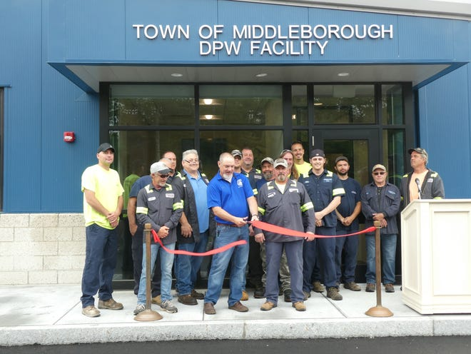 Middleborough Department of Public Works Director Chris Peck, seen here with DPW staff, does the honors Saturday at a ribbon cutting ceremony marking the opening of the new DPW facility on Sachem Street.