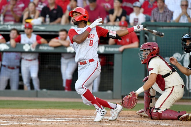 North Carolina State's Jose Torres (8) watches the ball after connecting for a home run against Arkansas during last Sunday's Super Regional game in Fayetteville, Ark.