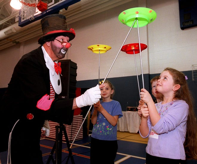 Frank Byrne as Rosie the Clown gets a little help on the spinning plates from Juleana Beutler, 7, left to right, Cody Rants, 5, and Victoria Rook, 6, on Saturday Nov. 16, 2002 at the annual Picnic in the Grove.