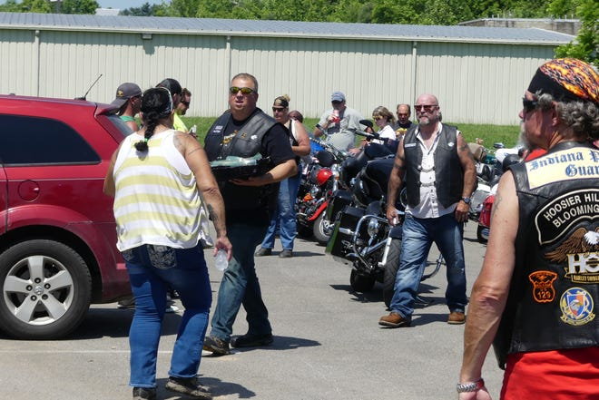 Barry Laird, center holding basket, offers cookies to the riders of the Dumon McCain Memorial Ride as they stopped at Jaycee Park. The refreshments were provided by the Azusa StreetRiders and Paoli United Pentecostal Church. The event benefitted Laird's grandson, Colton Laird.