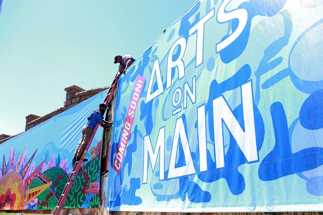 Derek Chave, left, and Aaron Christee hang wall covering on the wall at the corner of Fayetteville Road and Knox Stree, Tuesday, June 15, for the new CAE Arts on Main expansion, at 415 E. Main Street in downtown Van Buren.