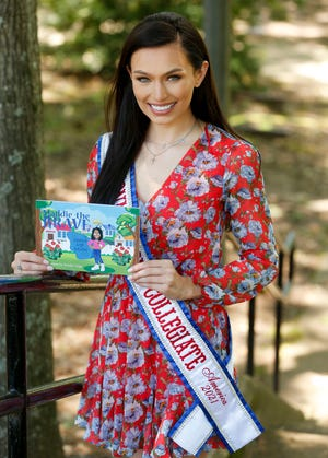 """Noelia Voigt, University of Alabama student and contestant in the Miss Collegiate America pageant, shows the book, """"Maddie the Brave,"""" she has written as part of her effort to stop bullying Tuesday, June 15, 2021, at Manderson Landing in Tuscaloosa. [Staff Photo/Gary Cosby Jr.]"""