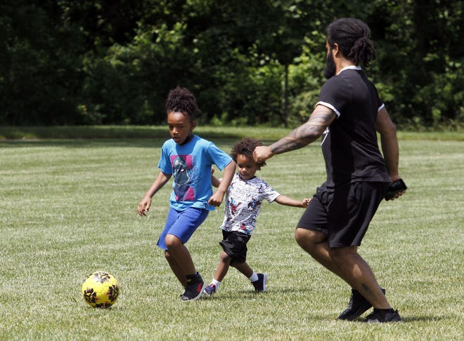 Max Bradley, 8, and his brother Princeston, 3, play soccer with their father, Devine, at Hannah Park on June 15.