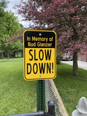 """A sign installed at the southeast edge of Clinton Elementary's playground implores motorists to slow down as they pass the school and travel on Clinton Heights Avenue in memory of Howard """"Bud"""" Glanzer Jr., who passed away May 30. Glanzer's house, seen in the background, neighbors the school and he was known throughout the neighborhood and by school staff and parents as a watchdog for students."""